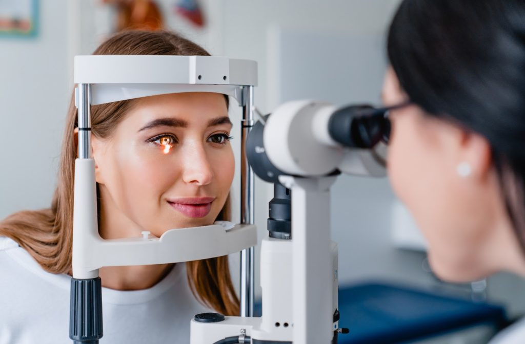 Woman with her forehead pressed against an eye exam machine that focuses a light on her eye while a doctor observes